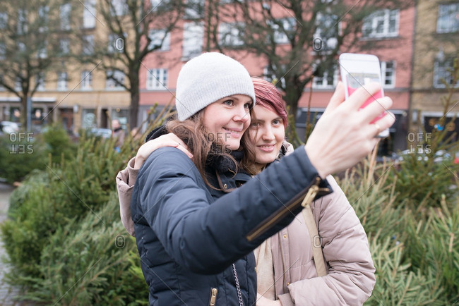 Mother taking selfie of her and her teen daughter while shopping for a Christmas tree