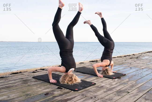 Two women doing headstands on a pier