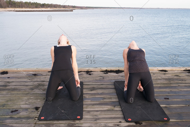 Two women doing yoga stretches on a pier
