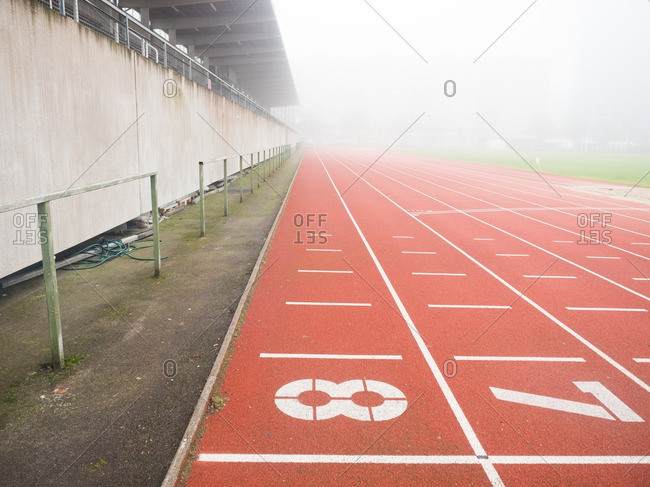 Lanes of an empty running track in the fog