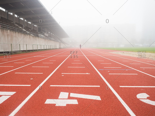 Distant person running on a track in the fog