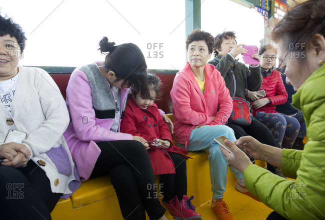 Beijing, China - March 24, 2016: Boat riders using their cellphones at the Summer Palace
