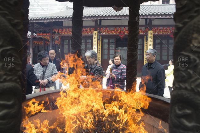 Shanghai, China - March 31, 2016: People and the flames of the fire pit at the Jade Buddha Temple