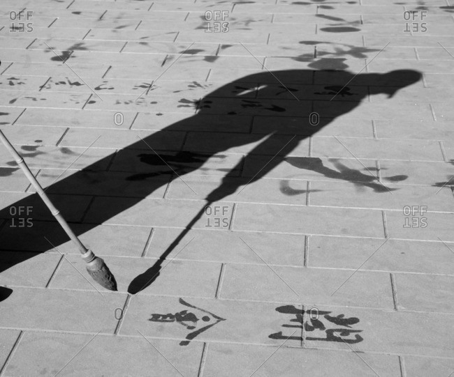Shadow of a calligrapher writing on a park sidewalk, Temple of Heaven, Beijing, China
