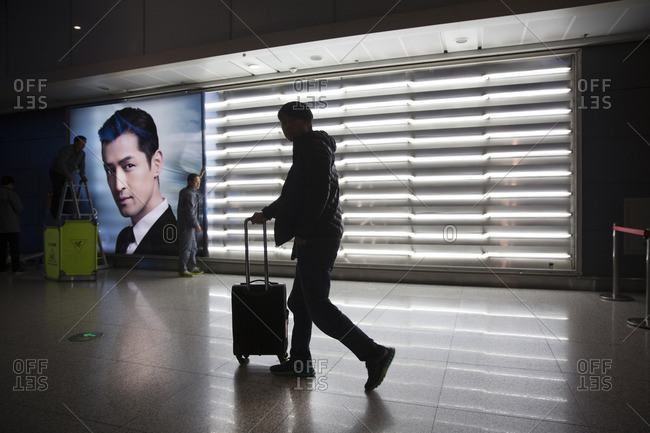 Beijing, China - March 25, 2016: Man pushing a suitcase by advertisements at the Beijing Capital International Airport