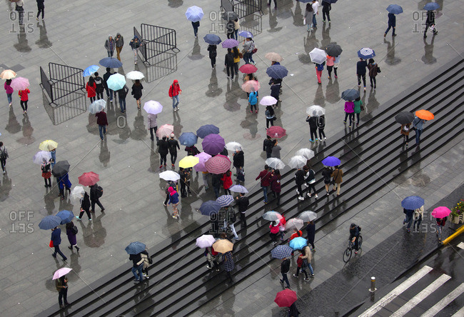 Shanghai, China - April 2, 2016: Crowd with colorful umbrellas in the rain on The Bund walkway