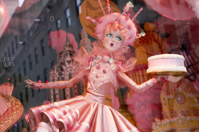 New York City, United States - December 6, 2016: Doll holding a cake in a store window display