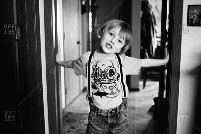Boy in suspenders and a t-shirt standing in a doorway