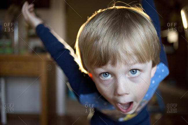 Boy swinging his arms behind him and opening his mouth wide