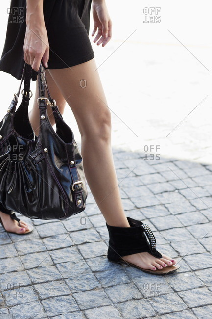 Low section view of a young woman wearing modern flat sandal and walking