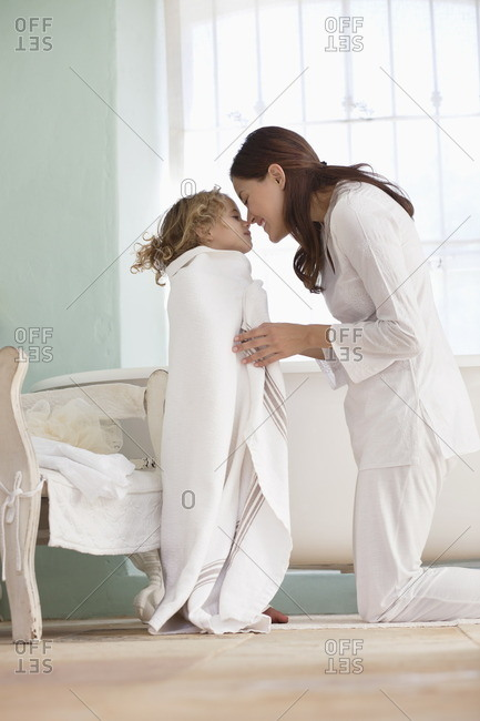 Woman rubbing noses with her daughter wrapped in towel after the bath