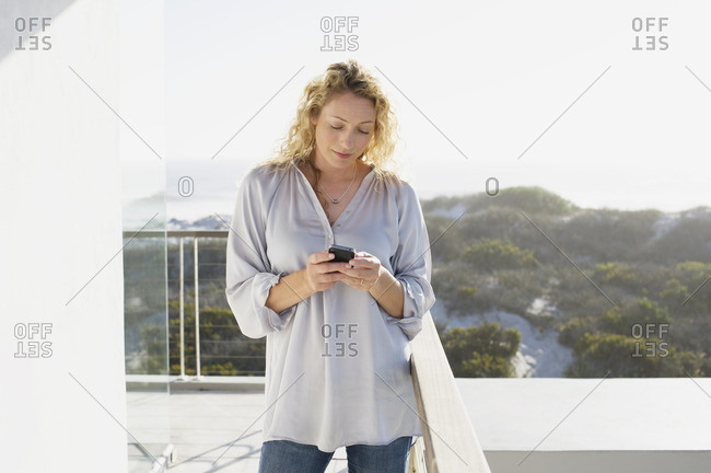 Mid adult woman text messaging with a mobile phone