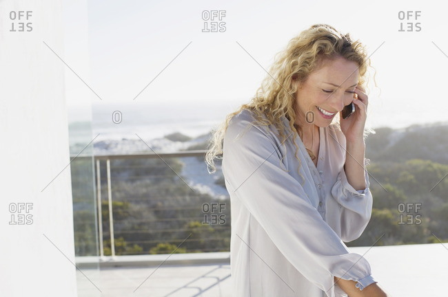 Mid adult woman talking on a mobile phone and smiling