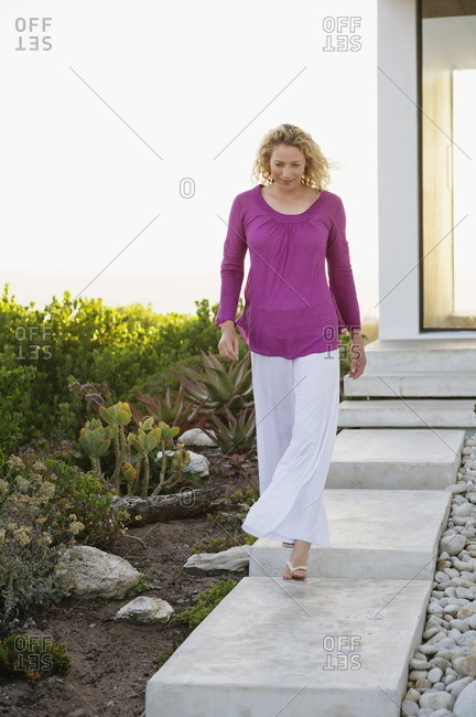 Mid adult woman walking against house