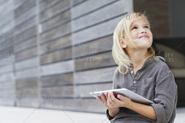 Girl holding a digital tablet and looking up