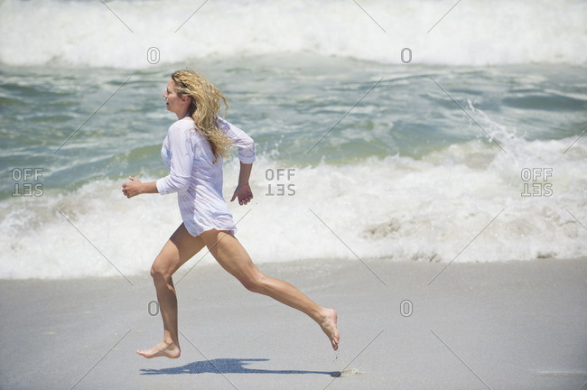 Side profile of a beautiful woman running on the beach