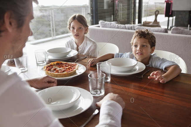 Man talking to children during meal time