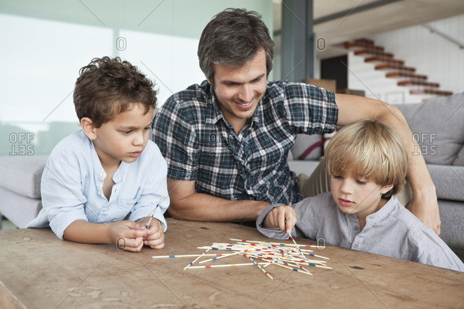 Boys playing pick up sticks with their father