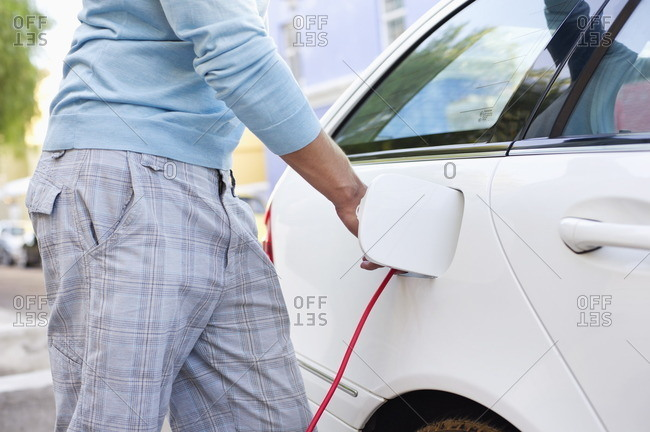 Mid section view of a mid adult man charging the electric car