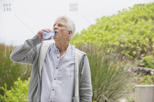Thirsty senior man drinking water