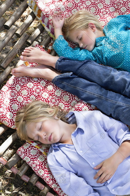 Tired little siblings sleeping in hammock