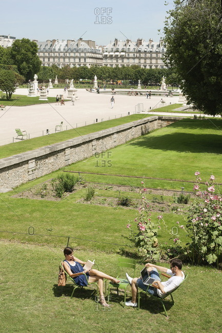 Man using a laptop with a woman reading a magazine in garden, Jardin des Tuileries, Paris, Ile-de-France, France