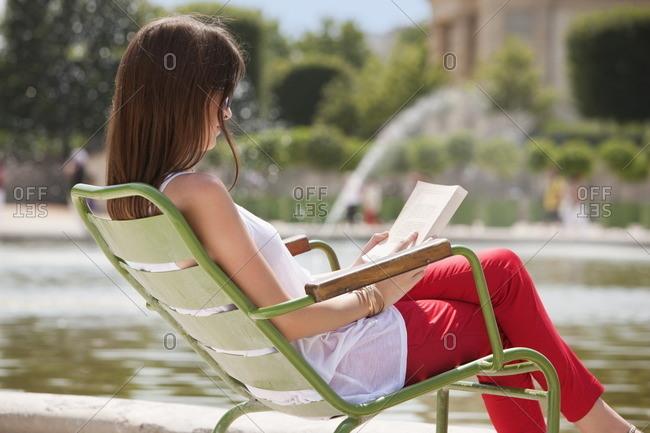 Woman reading a magazine, Jardin des Tuileries, Paris, Ile-de-France, France