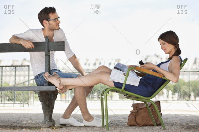 Woman using a mobile phone with a man sitting in front of her, Jardin des Tuileries, Paris, Ile-de-France, France