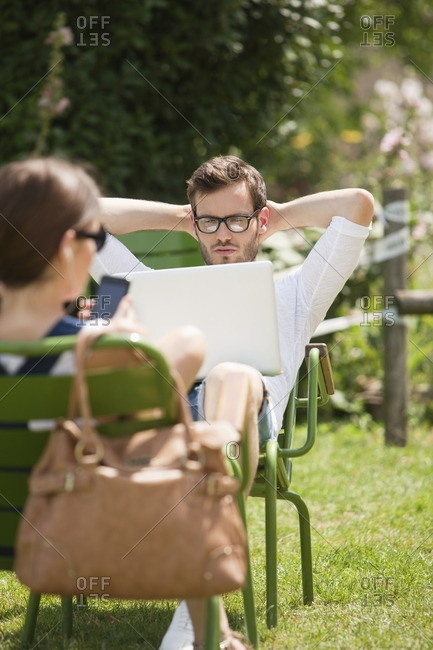 Man sitting in a garden and looking at a laptop, Paris, Ile-de-France, France