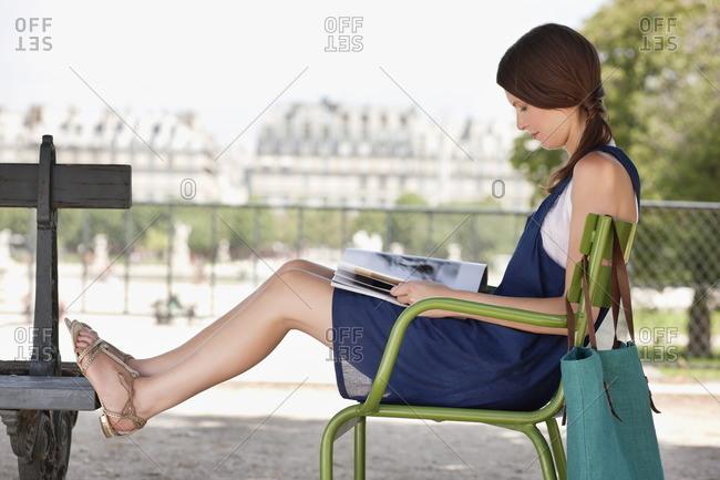 Woman sitting in a chair and reading a magazine, Jardin des Tuileries, Paris, Ile-de-France, France