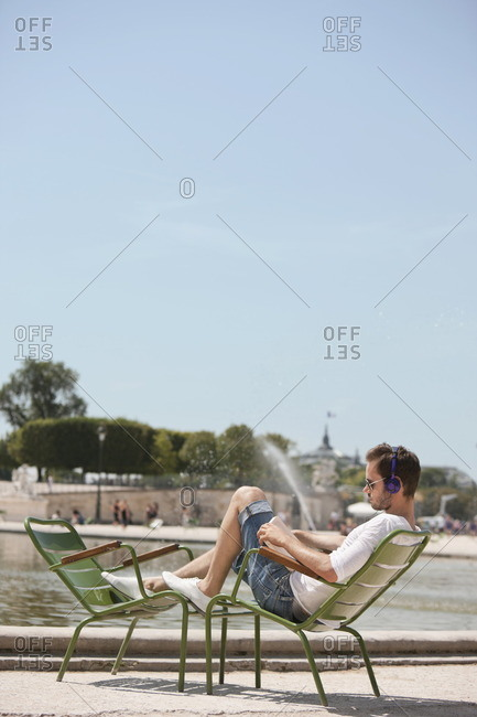 Man sitting in a chair and reading a magazine, Bassin octagonal, Jardin des Tuileries, Paris, Ile-de-France, France