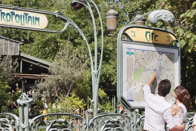 Couple pointing at a map, Paris, Ile-de-France, France