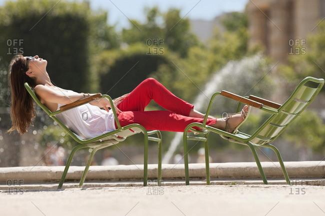 Woman resting in a chair near a pond, Bassin octagonal, Jardin des Tuileries, Paris, Ile-de-France, France