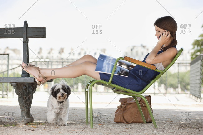 Woman sitting in a chair reading a magazine and talking on a mobile phone, Jardin des Tuileries, Paris, Ile-de-France, France