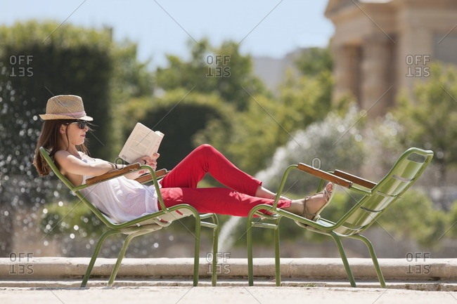 Woman sitting in a chair and reading a magazine, Bassin octagonal, Jardin des Tuileries, Paris, Ile-de-France, France
