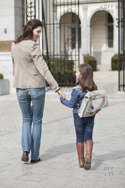 Girl with her mother walking to school