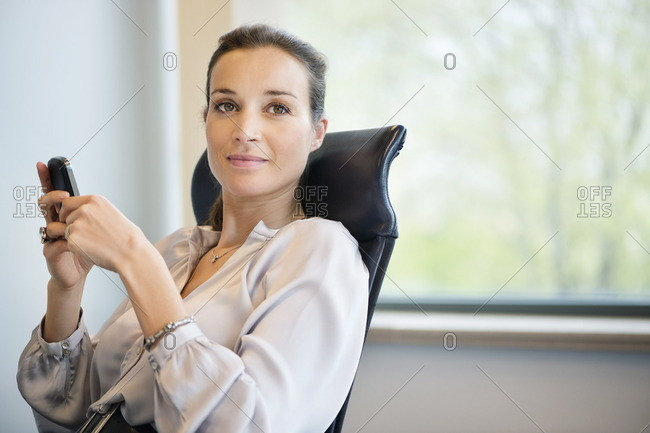 Portrait of a businesswoman text messaging on a mobile phone in an office