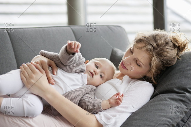 Woman resting on a couch with her daughter