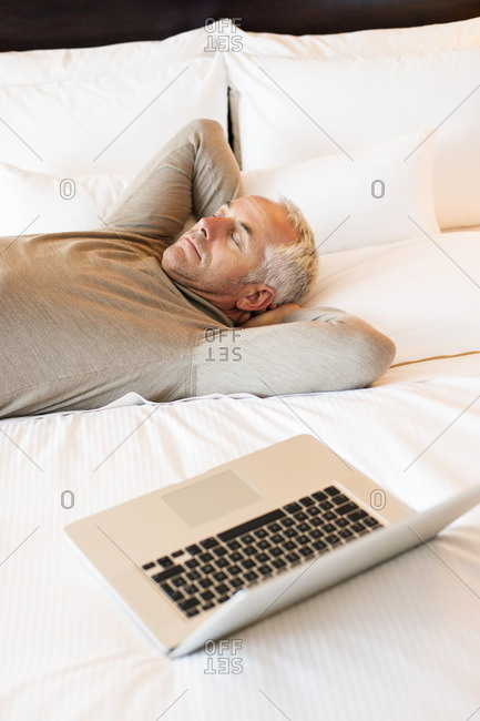 Man resting on the bed with a laptop in a hotel room