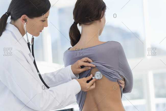 Female doctor examining a woman\'s back with a stethoscope