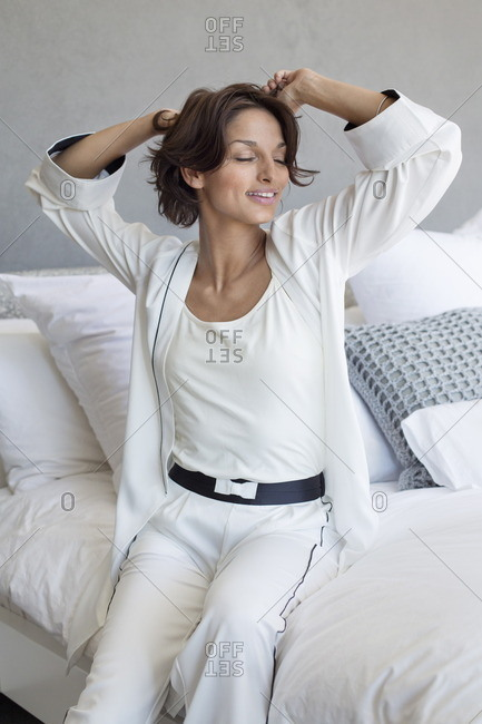Woman sitting on the bed and stretching her arms