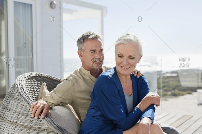 Couple sitting in a wicker chair romancing