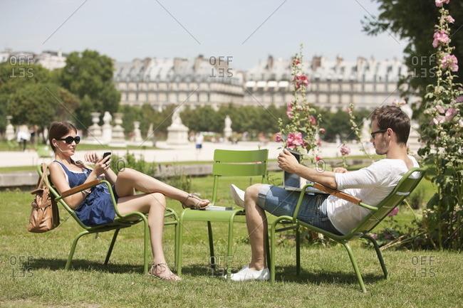 Man using a laptop with a woman talking on a mobile phone, Jardin des Tuileries, Paris, Ile-de-France, France