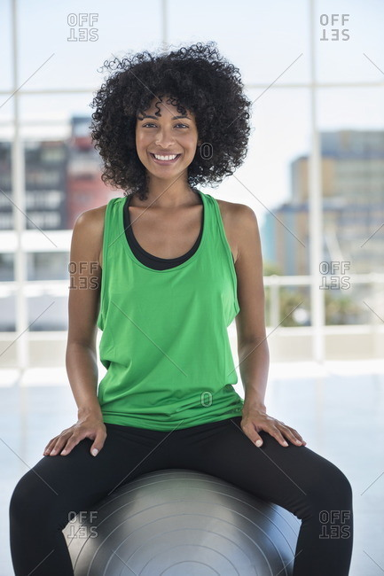 Portrait of a woman sitting on a fitness ball and smiling