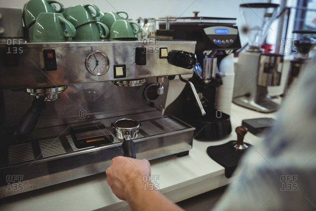 Mid section of man preparing coffee at coffee machine in the coffee shop