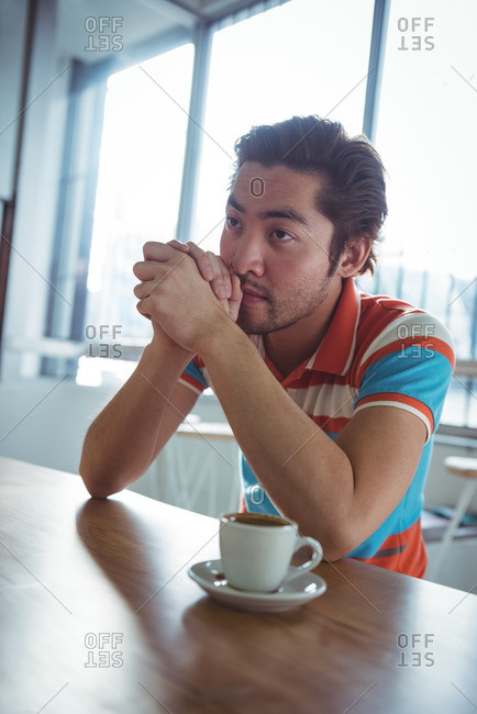 Thoughtful man sitting with cup of coffee on table in coffee shop
