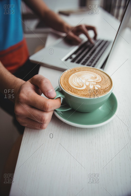 Mid-section of man using laptop and holding a coffee cup in coffee shop