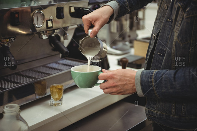 Mid-section of man pouring milk into coffee cup in coffee shop