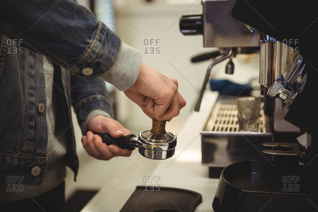 Mid-section of man pressing coffee with tamper in portafilter