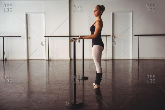 Thoughtful ballerina standing in ballet studio